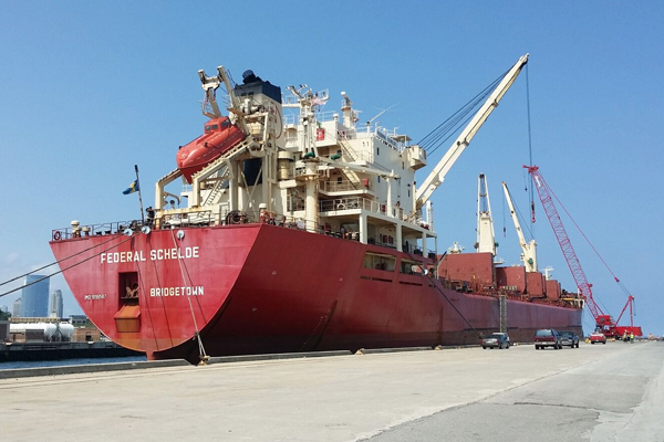 A ship dwarfs nearby cars and trucks. One of the port's mobile cranes is at the ship's bow. (Photo: Port Milwaukee)