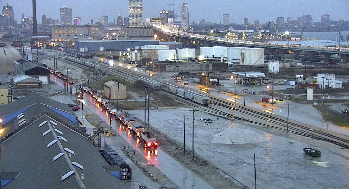 On a rainy day, trucks are lined up at the port, with several railcars on the adjacent sidings. (Photo: Port Milwaukee)