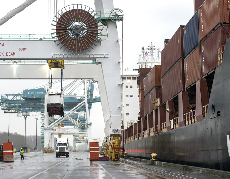 The tractor-trailer in this photo shows the immensity of the cranes and the ship it is passing. (Photo: Port of Portland)