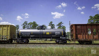A photograph of a two boxcara and a tank car on train tracks.