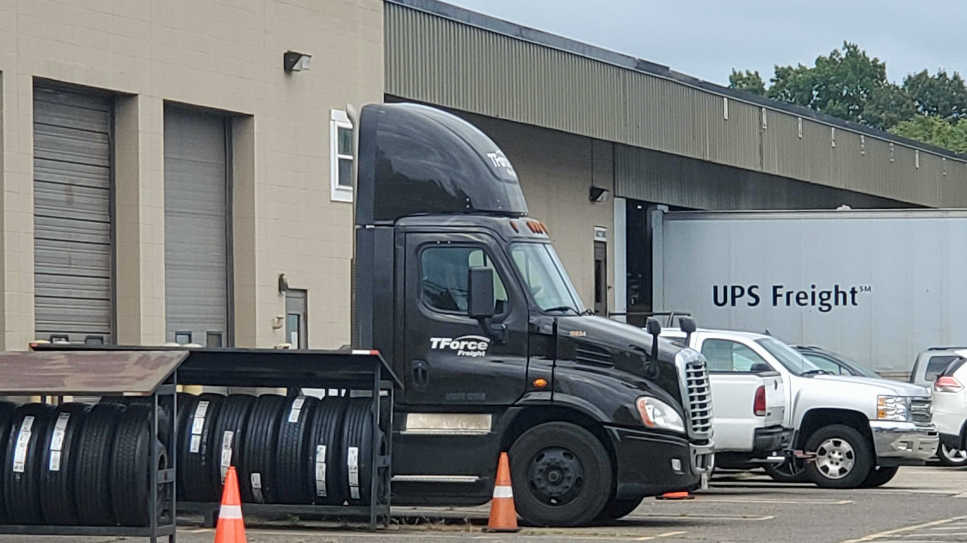 A parked TForce Freight truck with a UPS Freight in the background.