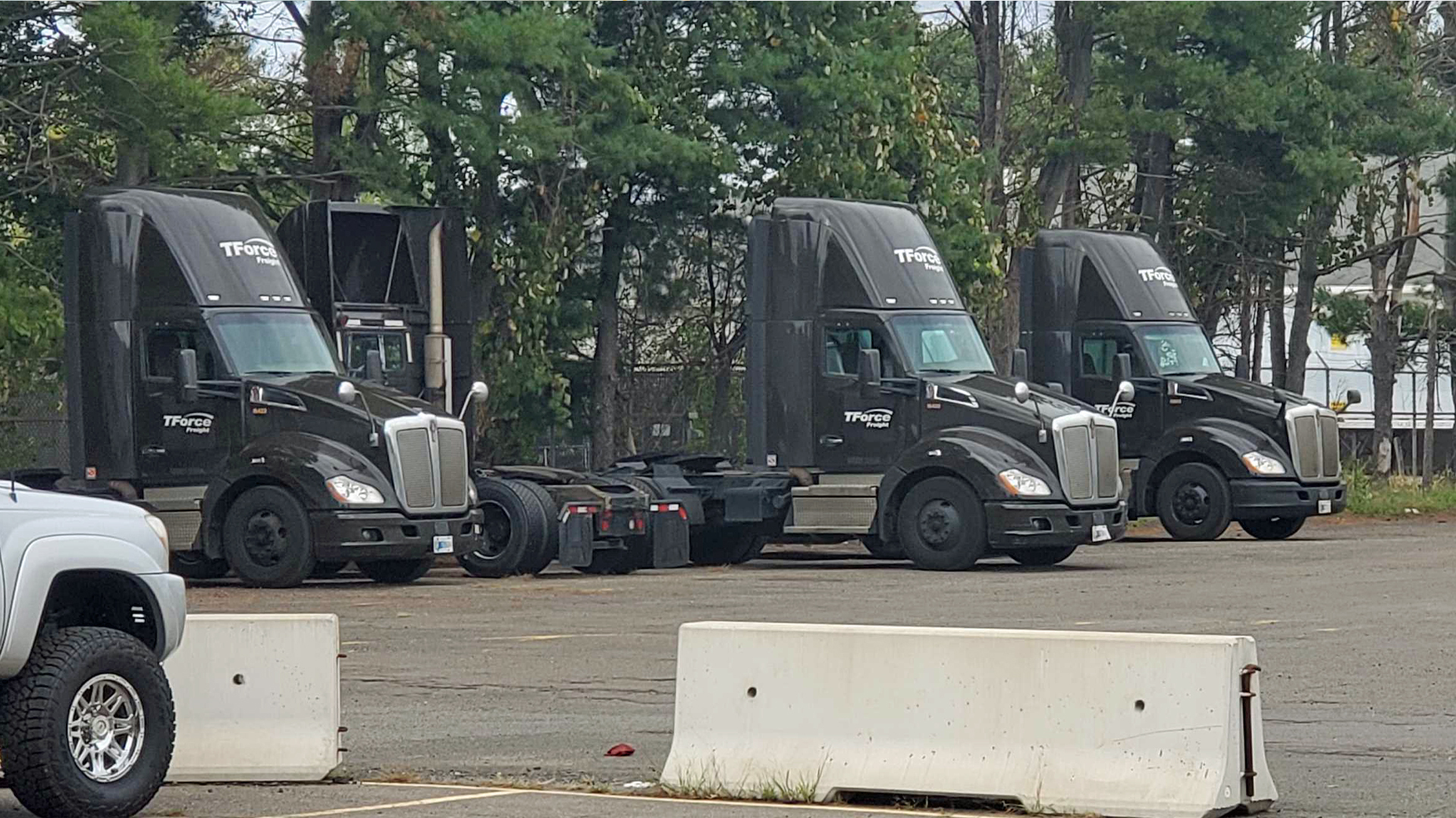 TForce Freight, owned by TFI International, trucks sit parked at a company facility. The Teamsters union has filed a complaint because TForce has limited the top speed of trucks.