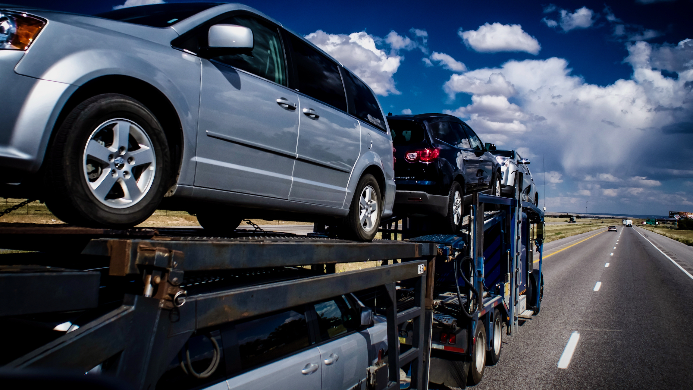 A truck transporting cars to viewed from the front right to illustrate an article about an acquisition by the company Trade X.
