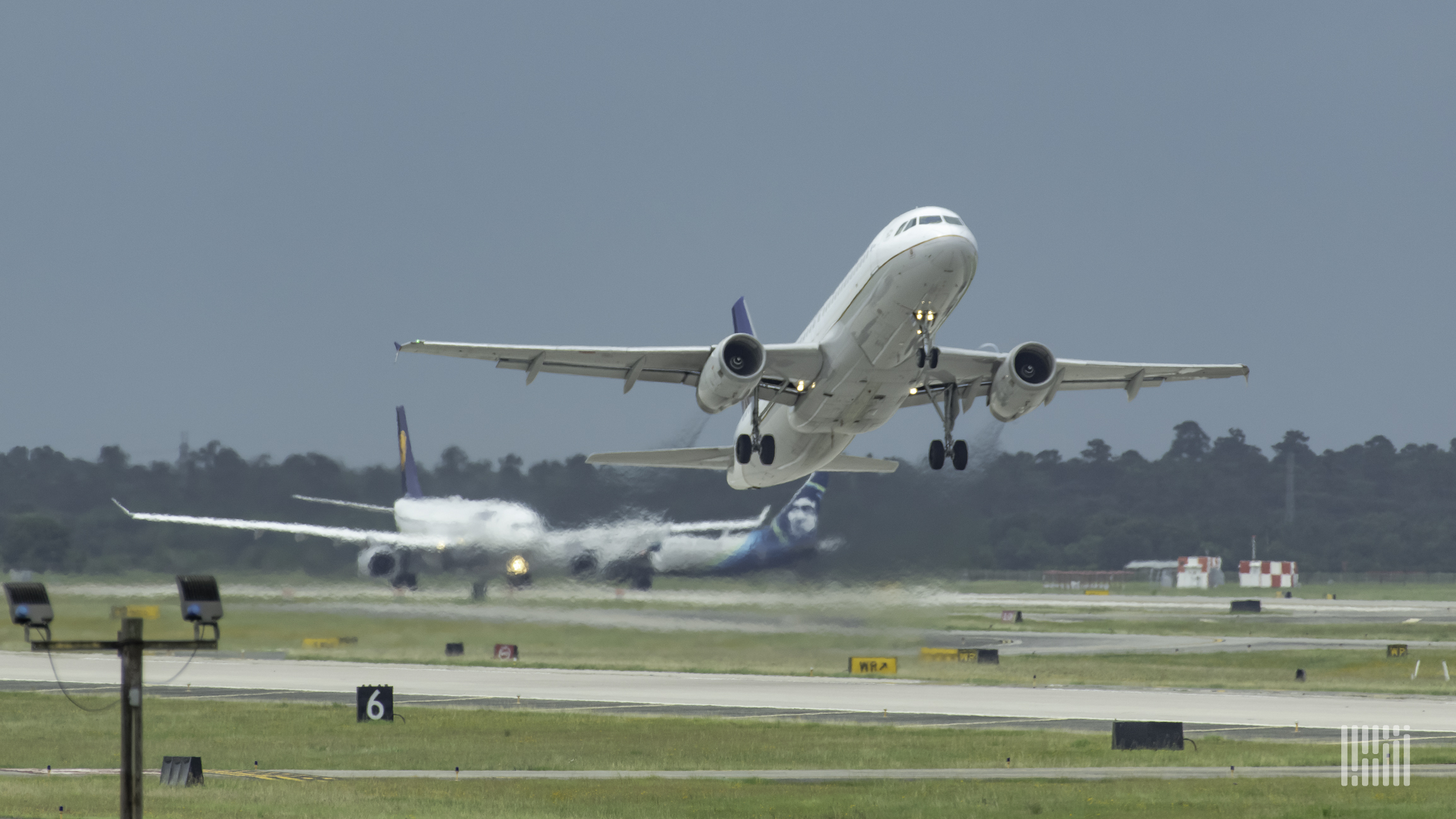 A white plane taking off, approach camera with underside visibile.
