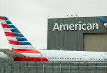 Tail end of a red, white and blue American Airlines jet close to an American hangar with the brand name on front.