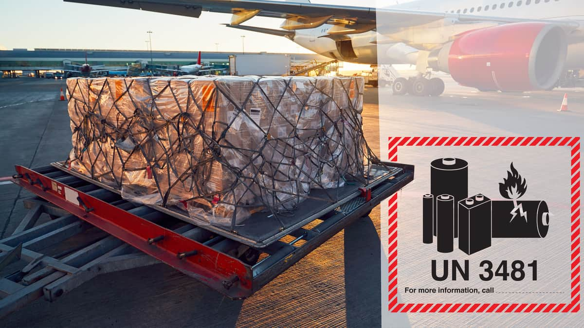 A pallet of cargo sits on tarmac near airplane with a hazardous goods warning label on it.