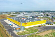 A big yellow warehouse with the DHL logo on the roof, looking down from above with an aircraft approaching in the distance.
