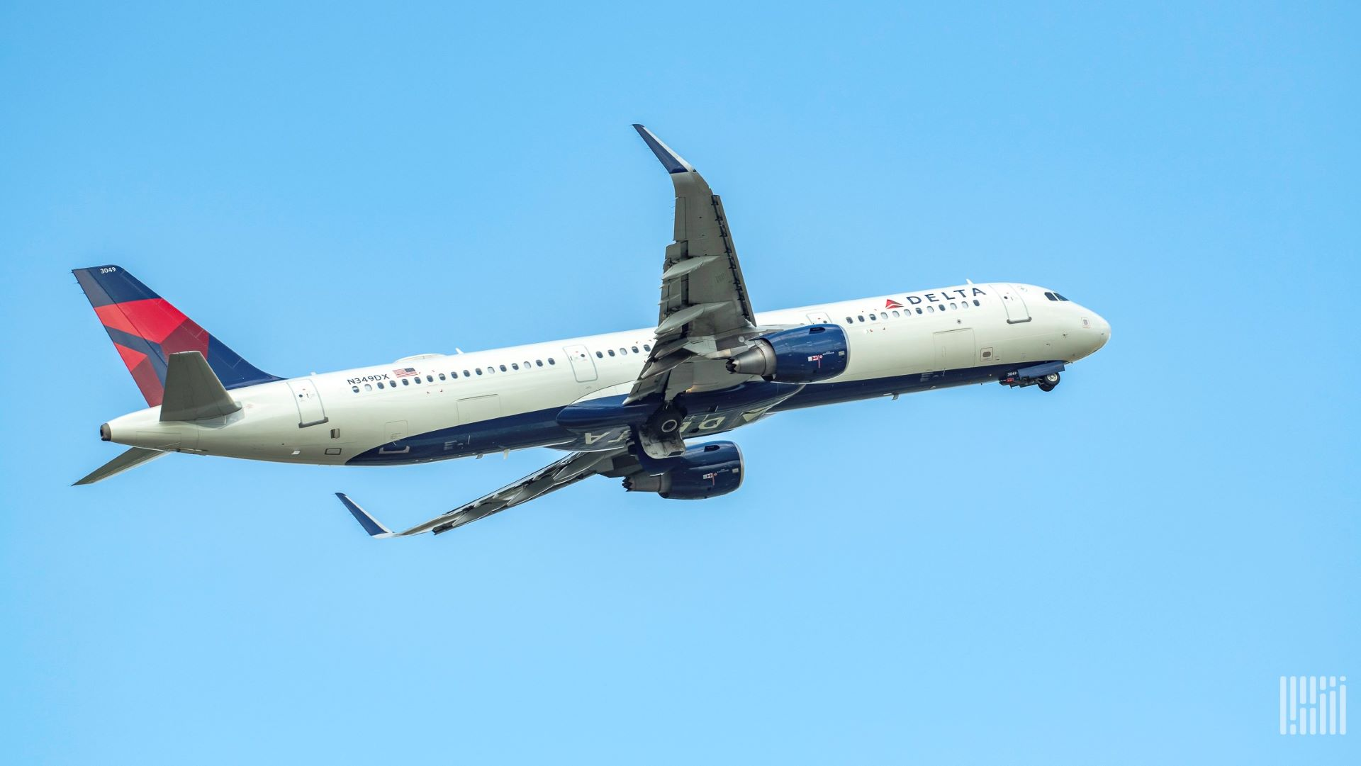 A white and blue-tailed Delta Air Lines jet flying upwards, view from below.