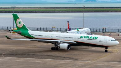An EVA Air A330 on the tarmac with a bod of water in the background.