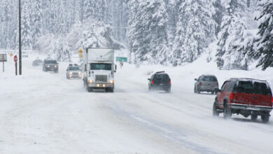 Cars and tractor-trailers on a snowy highway.