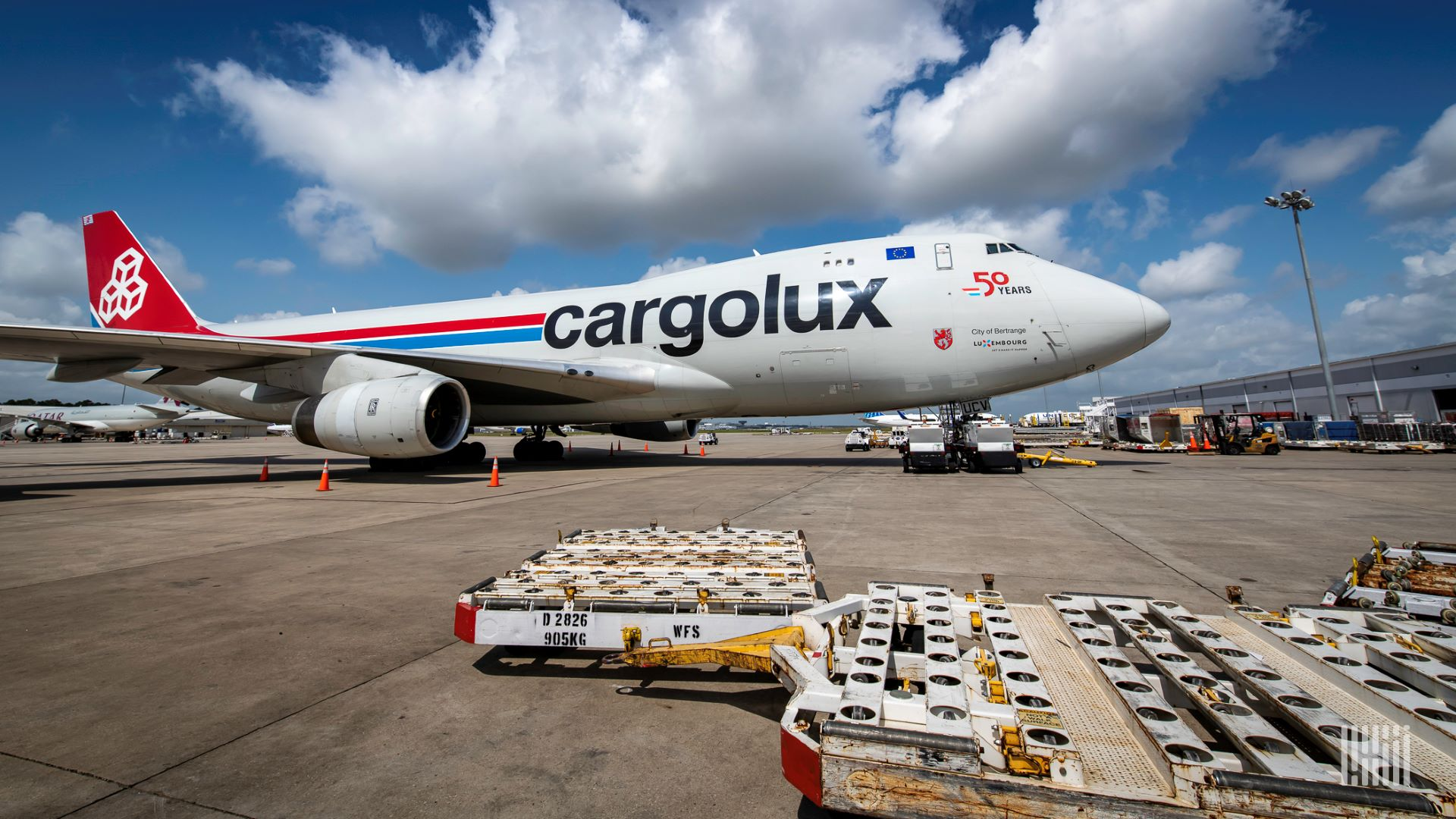 A Cargolux 747 cargo plane on the tarmac on a bright day with an empty pallet in the foreground.
