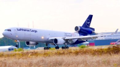 A white Lufthansa plane with a blue tail touches down on runway with grass in median.