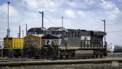 A photograph of a Norfolk Southern train parked next to a Union Pacific train.
