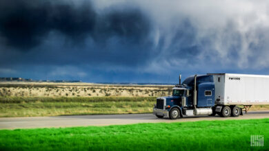 Tractor-trailer on a highway with dark storm cloud across the sky.