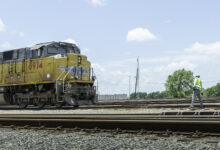 A photograph of a Union Pacific train traveling down a rail yard.