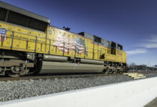 A photograph of a Union Pacific train rolling down a rail yard.