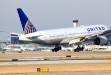 A white United Airlines jet takes off, view from the rear.