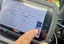 An electronic logging device screen being edited, with a finger being shown pushing a button on the screen.