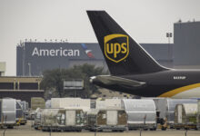 A UPS plane's tail at an airport with air cargo below to illustrate an article about cybersecurity reporting requirements for the rail and air sectors.