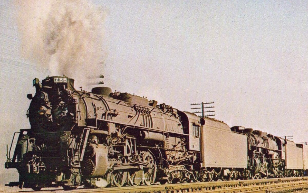 Two Nickel Plate Line steam locomotives lead a freight train through Fostoria, Ohio during the summer of 1958. (American-Rails.com)