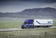 A tractor-trailer of Marten Transport travels on a highway with mountains in the background.