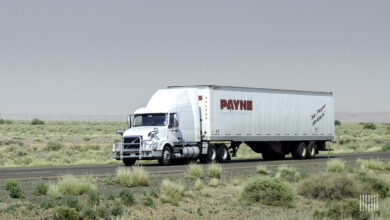 A tractor-trailer from Mullen Group trucking company Payne Transportation travels on a highway, viewed from the side of the road.