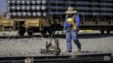 A photograph of a man looking at piece of railroad equipment in a rail yard.