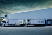 Tractor-trailers of XTL at a company load facility.